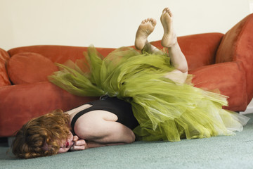 A woman lying on her front on the floor, wearing a lime green tutu, kicking her legs in the air.