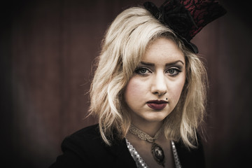 A young woman wearing a black top hat perched on the side of her head, and a black jacket. Circus clothes.
