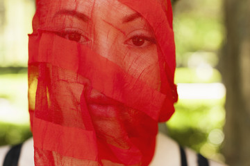 A young woman with a red see-through sheer veil across her face.