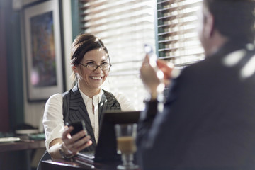 A man and woman working over lunch, seated at their desks. Smiling at each other, and holding smart phones.