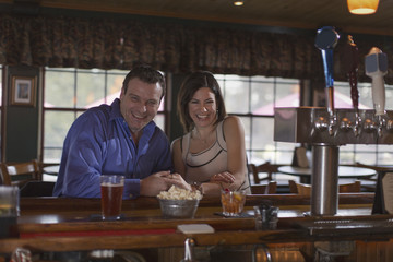 A man and woman side by side seated at a bar, smiling. On a date.