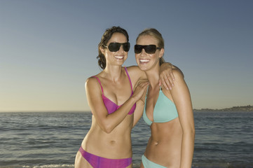 Two young women on the beach in Cape Town, wearing bikinis and sunglasses.
