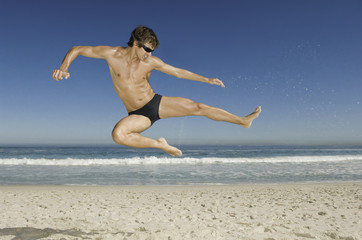 A young man doing a karate style leap on the beach in Cape Town.