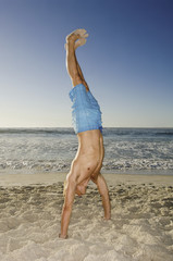 A young man doing a handstand on the sand in Cape Town.