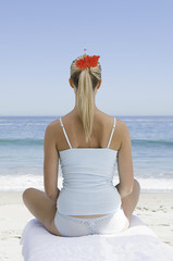 The beach. A young woman seated on a towel on the sand in a relaxed pose, looking out to sea.