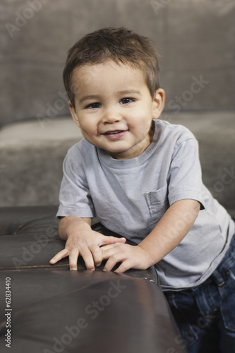 A child leaning on a brown chair, looking at the camera, smiling.