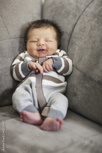 A baby propped up in the corner of a sofa.