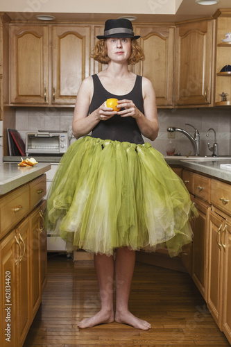 A woman wearing a lime green ballet tutu, standing in a ballet position in her kitchen.