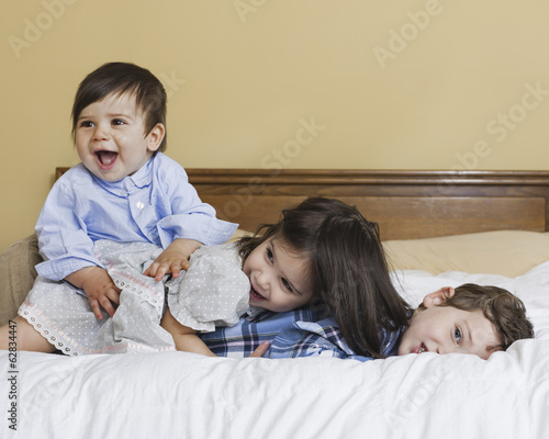 Three children in a family, lying playing on a large bed.