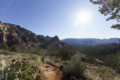 A woman in a sunhat walking up a trail in the Sedona national park, hiking in the midday sun.  Mountain landscape.