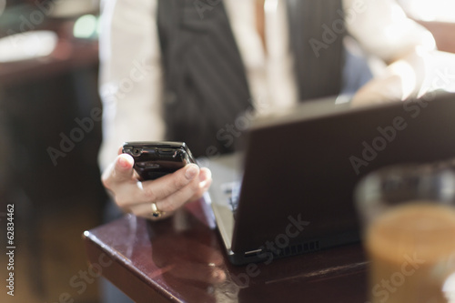 A woman seated at a desk holding a smart phone, with a laptop computer.