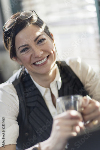 A woman holding a glass and smiling at the camera. A working lunch.