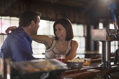 A man and woman seated at a bar, flirting and talking. On a date.