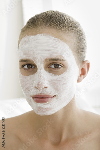 A spa treatment centre. A young woman with a white facial mask on her skin.