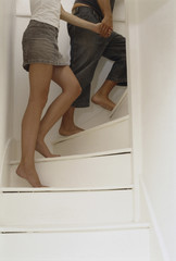 Two people, hand in hand, walking up the stairs.