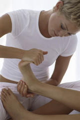 A woman holding a person's foot and massaging and flexing the toes.