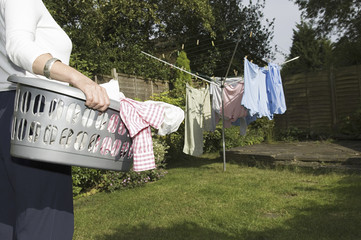A woman carrying a basket of washing out to the washing line.