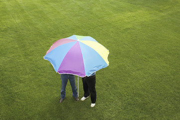 Two people under a striped umbrella on a lawn.