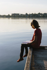 A young girl sitting on a dock, reading a book.
