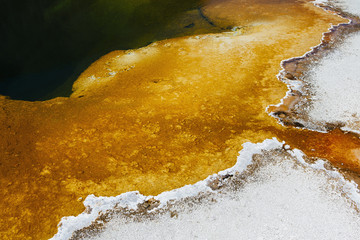 Detail of colorful water mineral deposits and rock formations from Midway Geyser, in Yellowstone National Park.