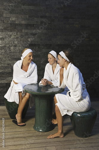 Three women seated around a table in a health spa