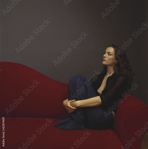 A woman dressed in black seated on a red couch.