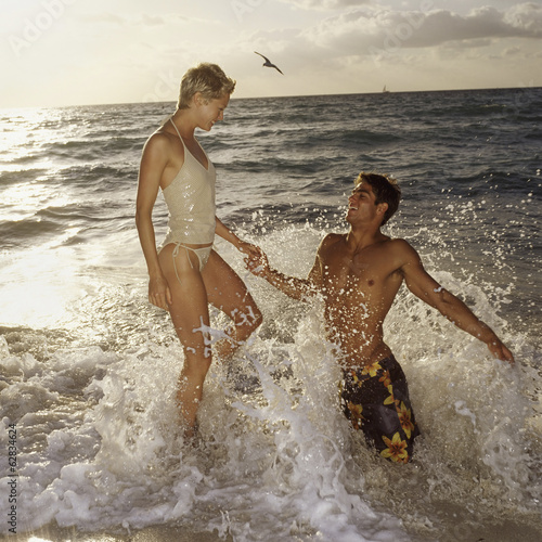 A couple in the sea, leaping in the surf at sunset. A man kneeling in the water.