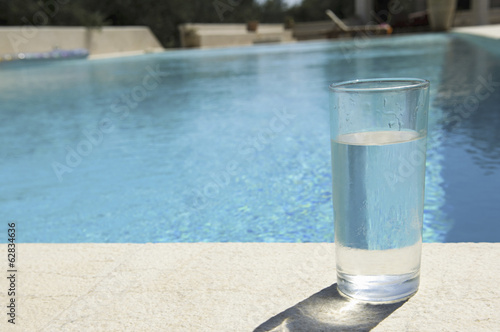 Glass of water on the side of a swimming pool