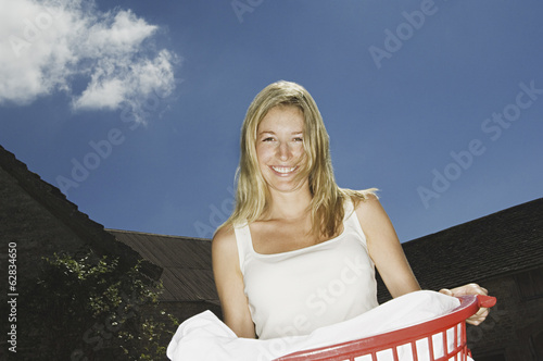 A woman holding a basket of washing.