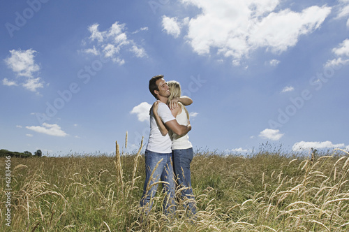 A couple standing in a field of wheat hugging.