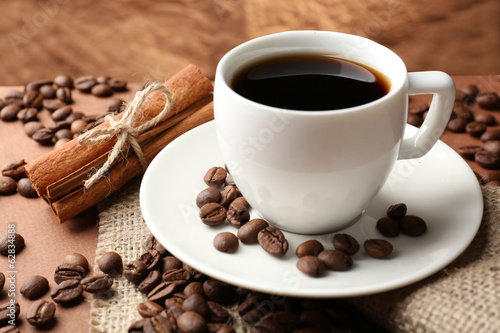Fotobehang Cafe Coffee beans and cup of coffee on table on brown background
