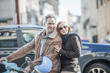 handsome couple riding a trendy scooter