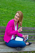 woman with laptop on park bench