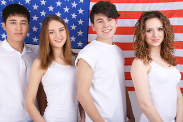 Group of beautiful young people on background of American flag