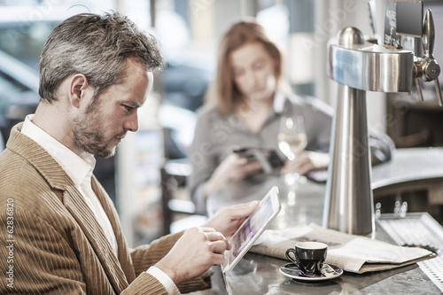 handsome man sitting in a bar and using a digital tablet