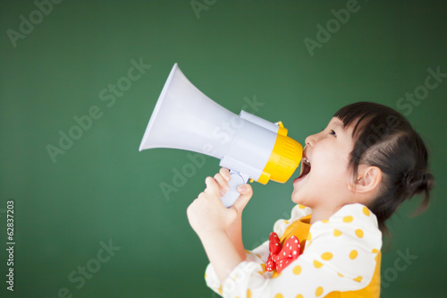happy child  using a megaphone with blackboard