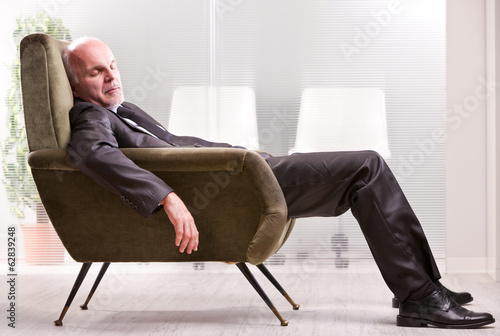 mature businessman asleep on an armchair