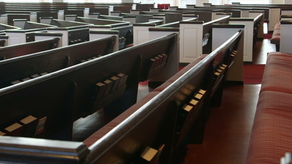 Camera slowly moves past wooden pews in a Christian church