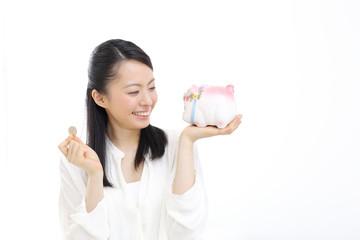 硬貨と貯金箱を持つ女性