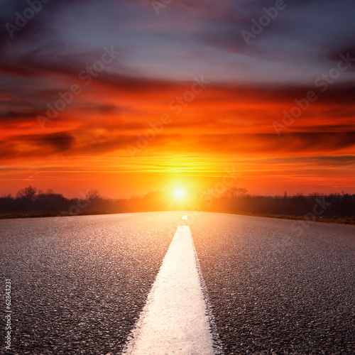 Driving on an empty asphalt highway towards the setting sun
