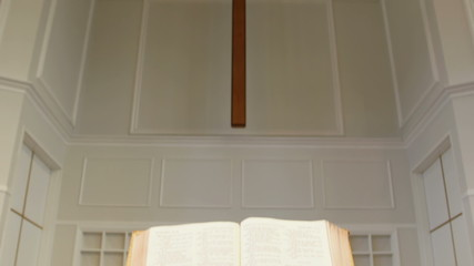 Tilt from open bible to cross on wall of church