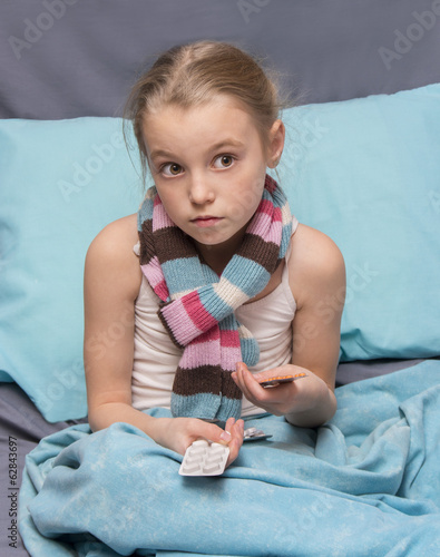 Sick child with pills in hand