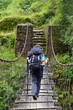 Trekker passing on a suspension bridge in the Himalayas