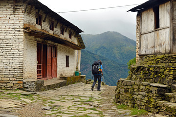 Trekker with backpack in a mountain village