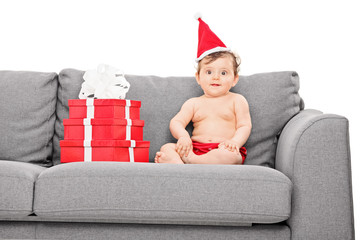 Baby girl with santa hat seated on couch