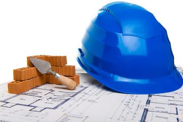 Ziegelmauer mit Bauhelm und Bauplan