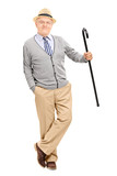 Senior gentleman with cane, leaning against a wall