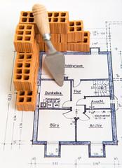 Ziegelmauer auf Bauplan mit Spachtel