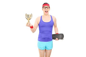 Man in sportswear holding trophy and a skateboard