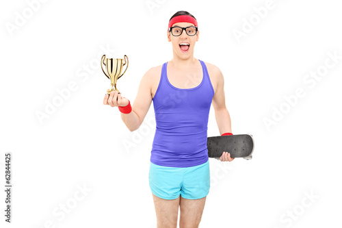 Man in sportswear holding trophy and a skateboard